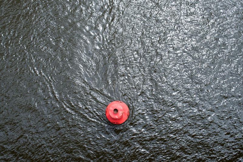 Red buoy on the water surface. Red round buoy on the water surface. View from above stock photography