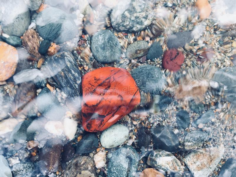 Red and Burgundy Jasper underwater. And after rain. Beautiful multi-colored stones stock photo