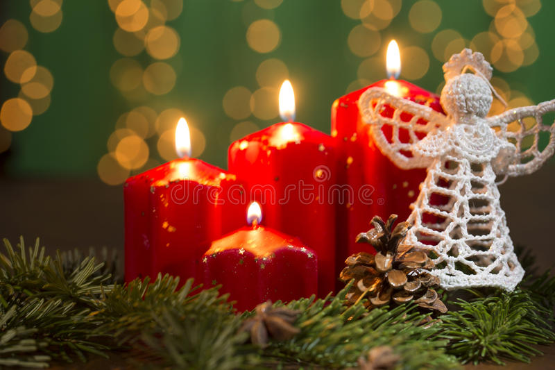 Red burning advent candles with crochet angel and pine tree still life. Red advent candles on the old wooden background with christmas light curtain stock photo