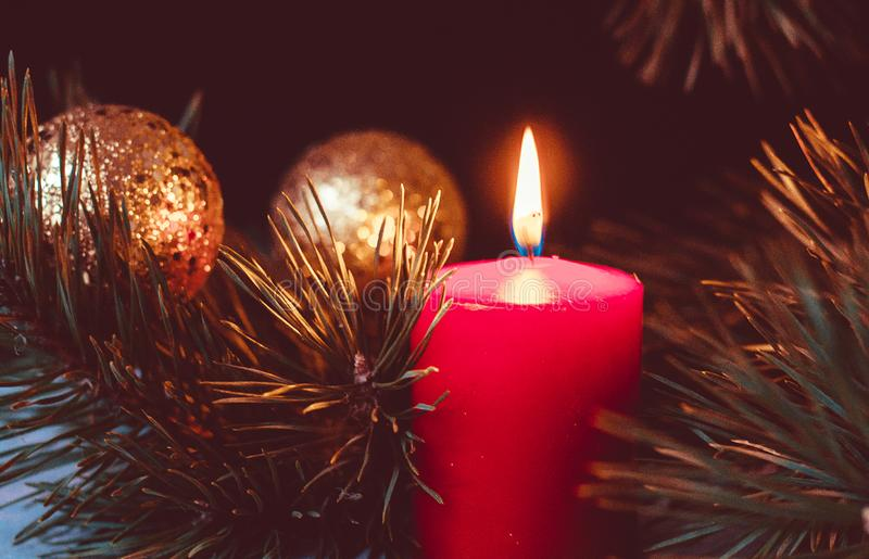 Red burning candle of an Advent wreath with fir branches and golden christmas balls on a black background. Vintage photo processing royalty free stock photos