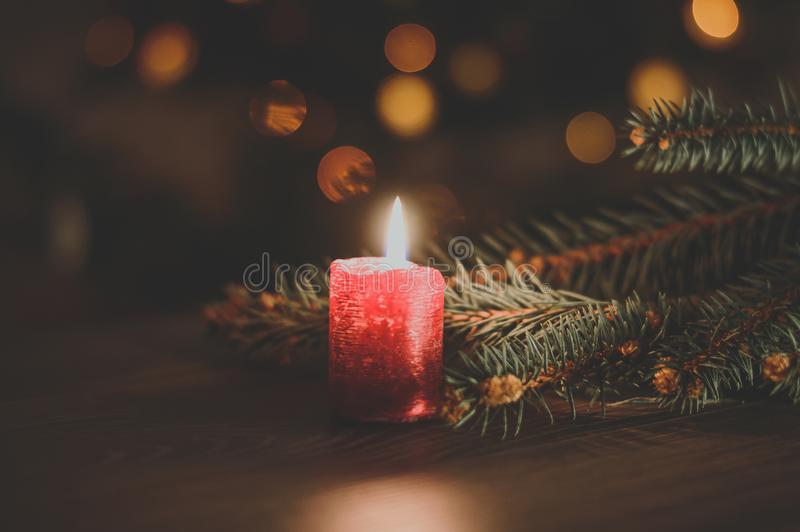 Red candle on Christmas tree background royalty free stock photography