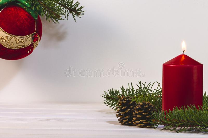 Red burning candle with pine cones and fir tree, winter decoration card with copy space for text stock photo