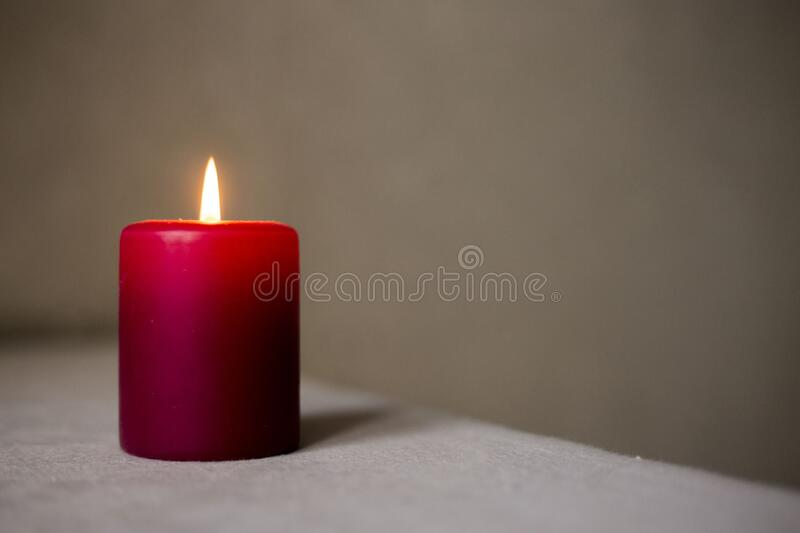 Red burning wax candle. Soft romantic light of flame stock images