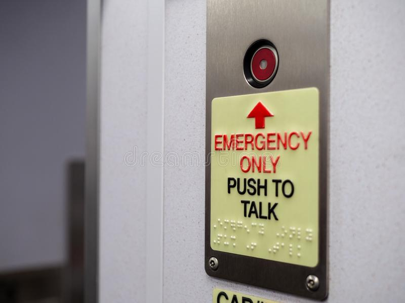 Red button with emergency only push to talk text with braille. Red button with emergency only push to talk notice with braille royalty free stock image