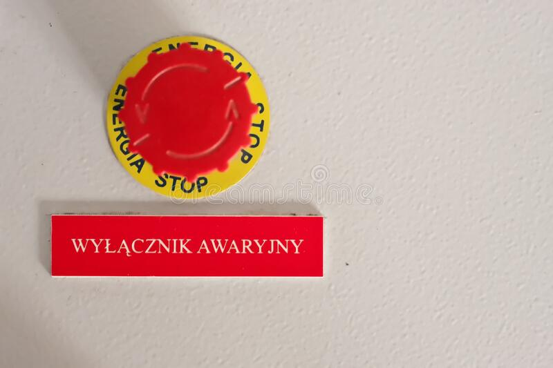 Red button with inscription plate `emergancy button` on the electrical cabinet in Polish language. stock photo