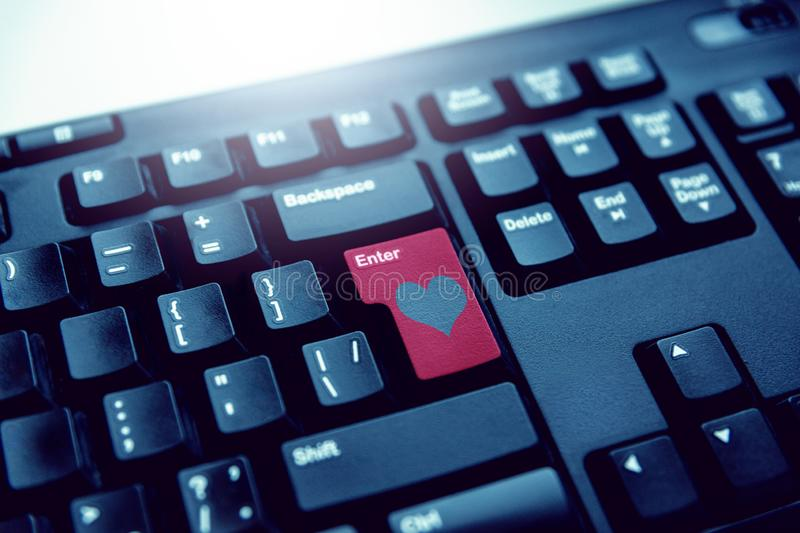 Red button on the keyboard with a heart enter. Online love royalty free stock photos