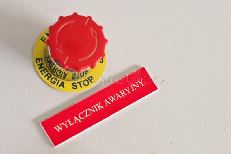 Red button with inscription plate `emergancy button` on the electrical cabinet in Polish language. royalty free stock images
