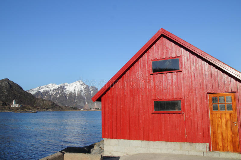 Red cabin and Stamsunds Church. Wooden cabin on the beach of Stamsund in Lofoten, the Stamsund church on the background stock photo