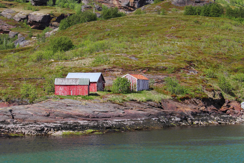 Red cabins on the shores of Birds island. Red cabin of Birds island (Fugloeya), a turistic Place above Norwegian polar circle royalty free stock images