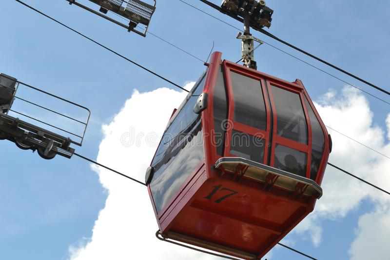 Red Cable Car with Blue Sky In Background. Cable Car ride/passenger lift with blue sky and clouds scene from Butlins entertainment Resort, in Minehead, England stock image