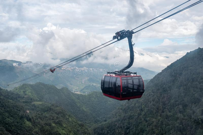 Red cable car sightseeing Sapa village in valley. Through of fog royalty free stock image