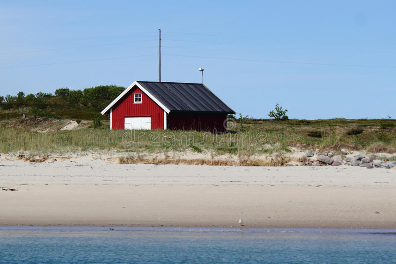 Red cabin on the beach of Birds island. Red cabin of Birds island (Fugloeya), a turistic Place above Norwegian polar circle royalty free stock images