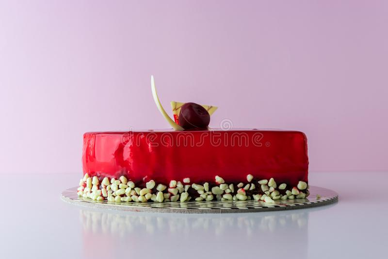 Red cake with nuts on pink background. Minimal holiday concept.  royalty free stock photo