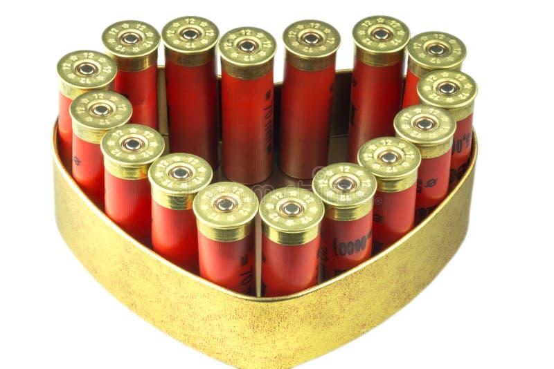 Red 12 caliber bullet shotgun shells in tin heart shape box. Gift for real man. stock photography
