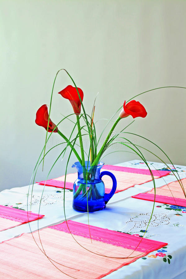 Red callas on blue vase. Arrangement of three red calla flowers on blue vase with handle; on table covered with hand-embroidered white linens and pink rimmed royalty free stock photography