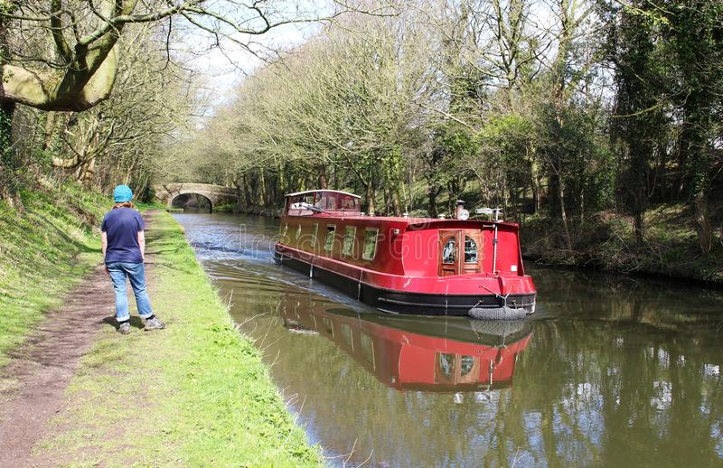 Red canal boat and walker on towpath Lancaster canal stock images