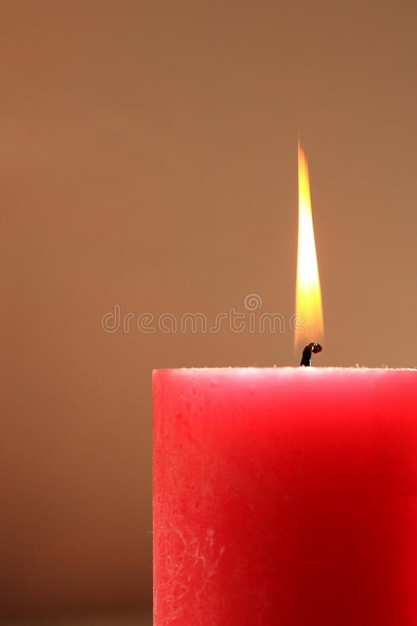 Red candle. A single burning red candle royalty free stock photo
