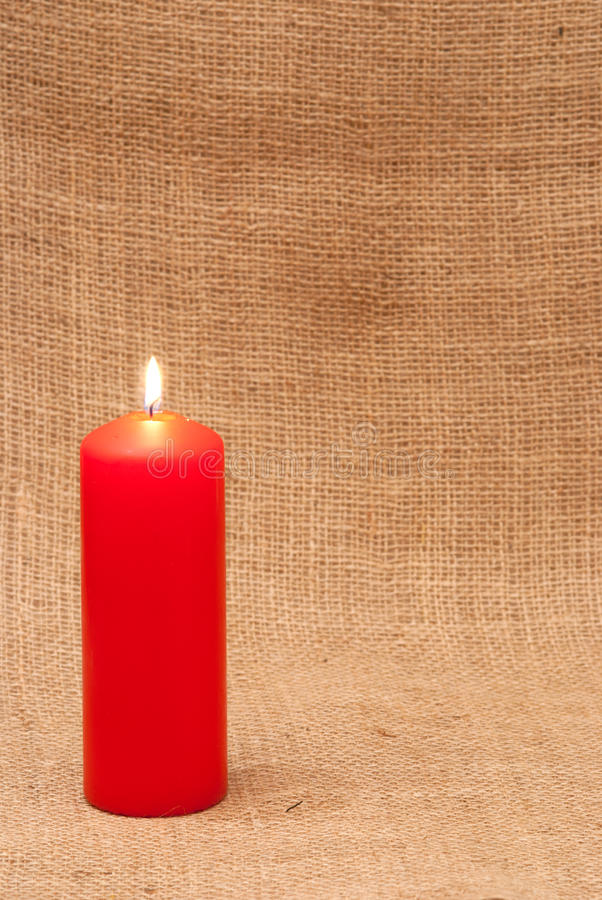 Red Candle. A red candle on the background of a piece of hessian canvas royalty free stock images