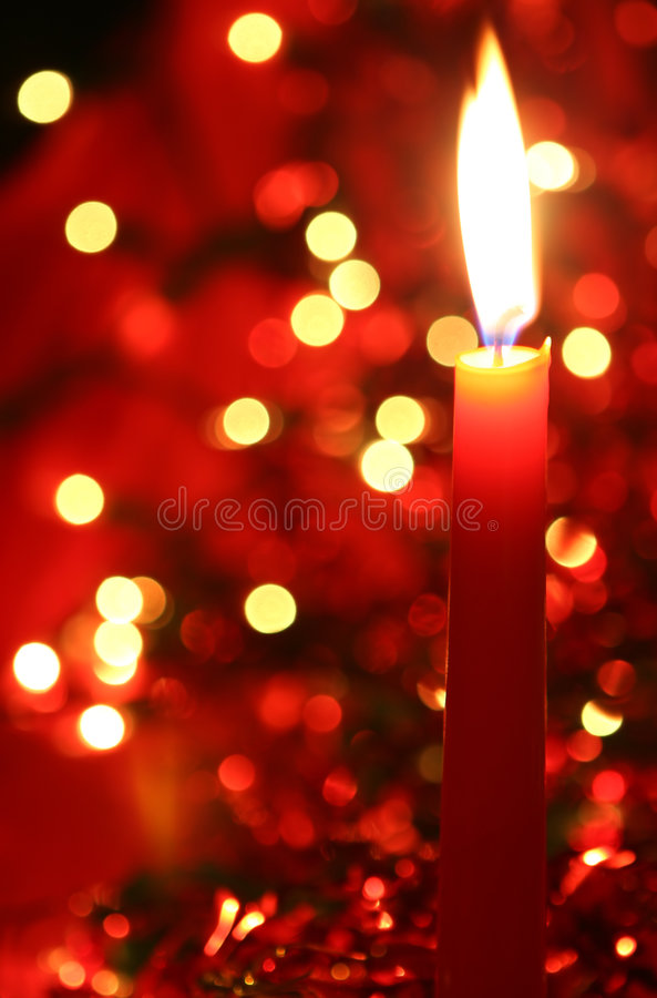 Red Candle. Red Christmas candle, with colorful lights and tinsel in the background. Shallow depth of field royalty free stock photo