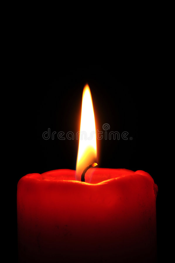 Red candle. Burning red candle in front of a black background royalty free stock photos
