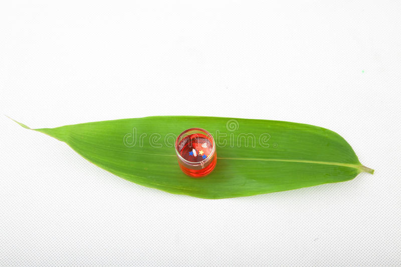 Red Candle on a bamboo leaf royalty free stock image