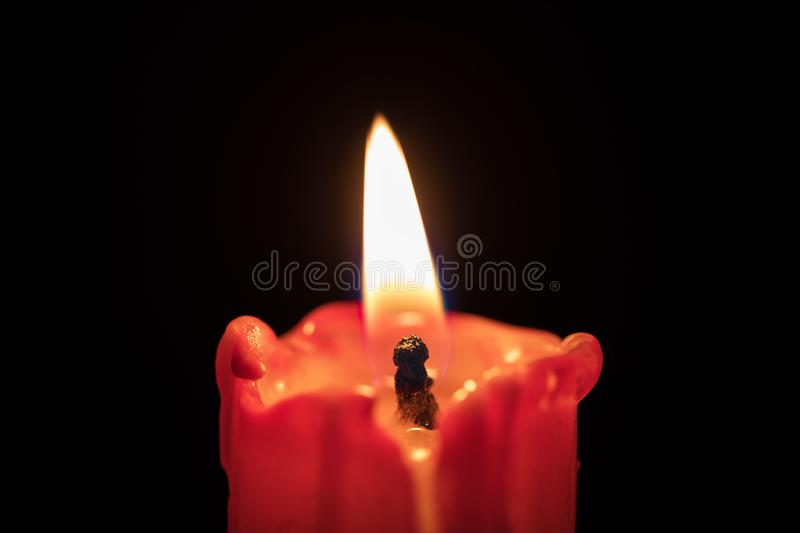Red candle on black background, flame extreme closeup. Macro royalty free stock photography