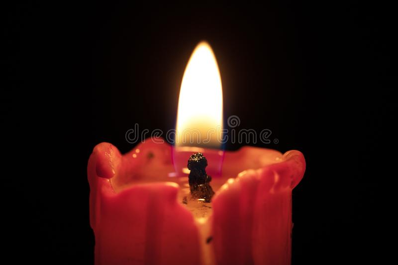 Red candle on black background, flame extreme closeup. Macro royalty free stock image