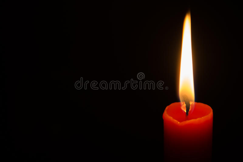 Red candle in the dark. One red lit candle isolated on a black background stock images