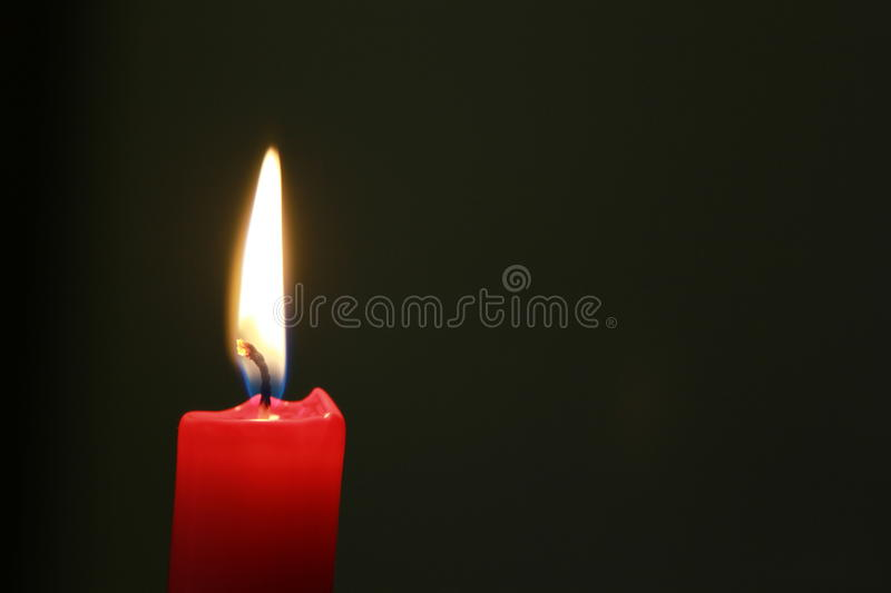 Red Candle with flame and dark background, copy space. Red candle with flame, illuminating the darkness royalty free stock image