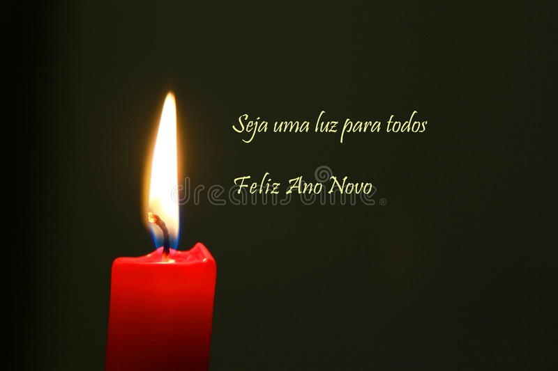 Red Candle with flame and dark background, portuguese text royalty free stock photo