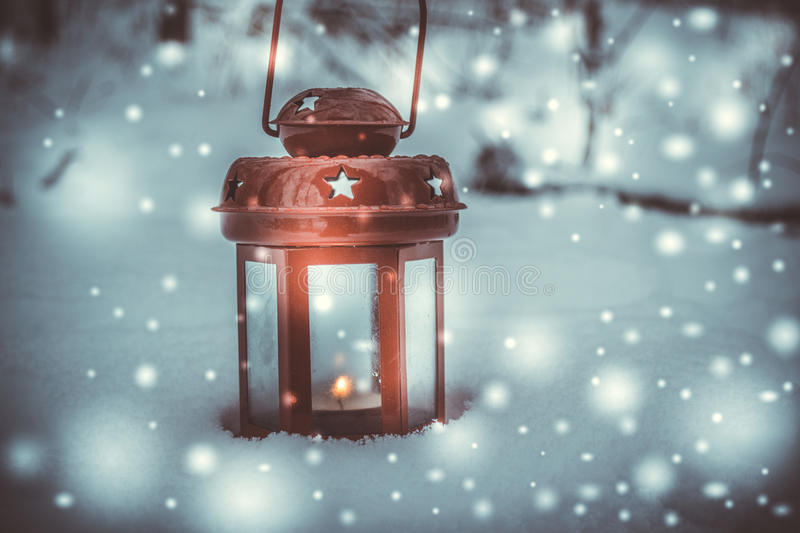 Red candle lantern with candle in snow during snowfall. Christmas Winter New Year background Scenery royalty free stock images