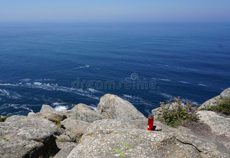 Red candle lantern flame abandoned upon sea boulders of Cape Finisterre stock images