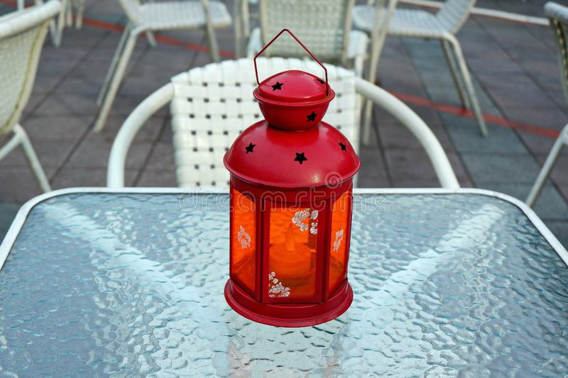 Red Candle Lantern on the White Glass Table. Closeup Photo of Red Candle Lantern on the White Glass Table stock photo