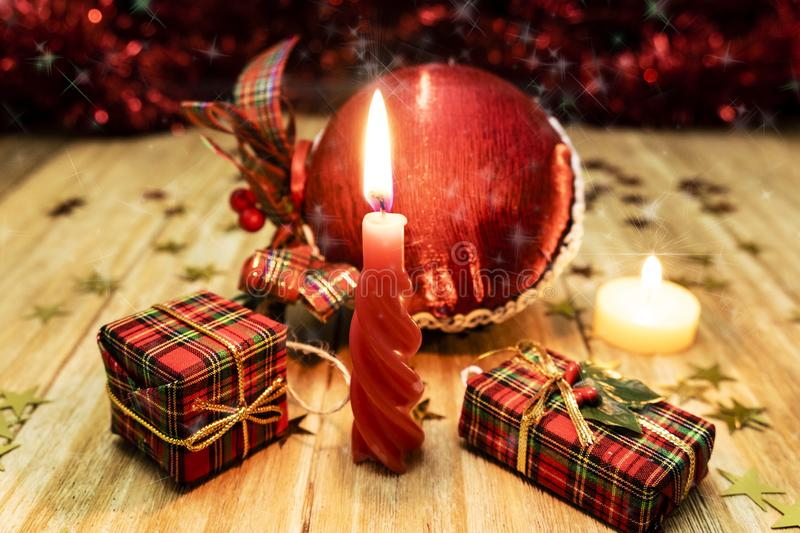 Red candle lit next to some packages of gifts and a red ball of Christmas ornament stock photography