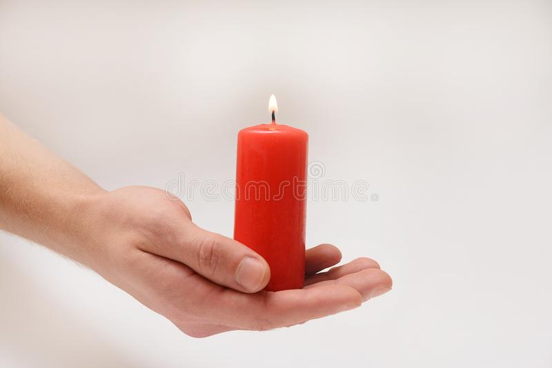 Red candle in loving hands. Man holding a red candle in his hands on a white background royalty free stock photography