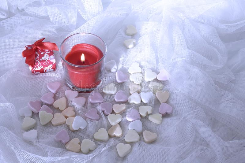 Red candle , pink and white candies on white satin background, valentine`s day concept. Red candle , pink and white candies on white satin background.Valentine` royalty free stock image