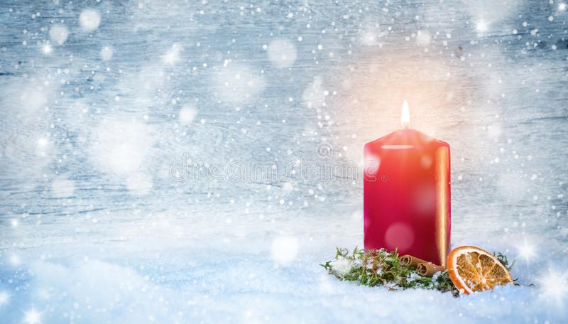 Red candle with warm light in the snow. Red candle decorated with moss, cinnamon and a slice of a dried orange standing amidst a snowy surrounding with a light royalty free stock photo