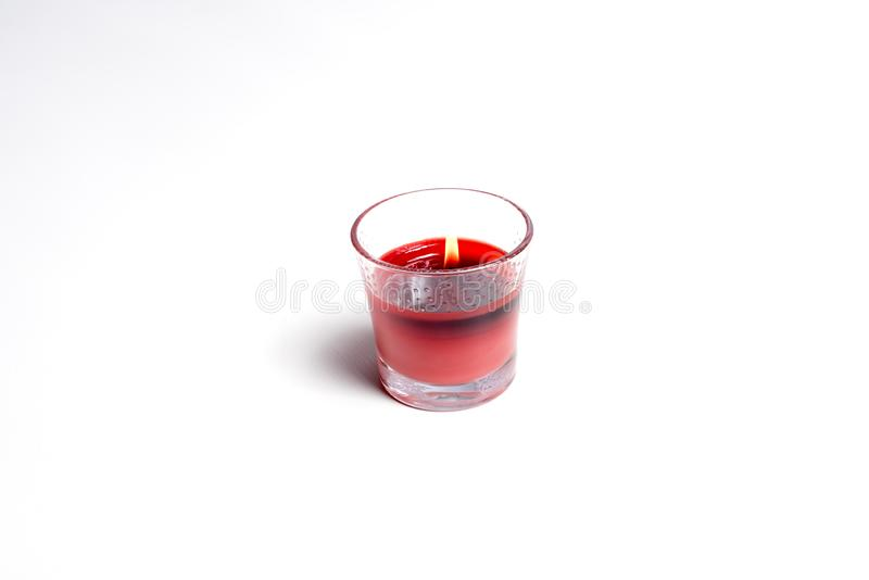 Red candle on white. Red candle in glass holder. Candle is lit. All on white background royalty free stock images