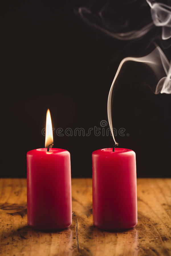 Red Candles. Burning And Blown Out Candle with Smoke stock image