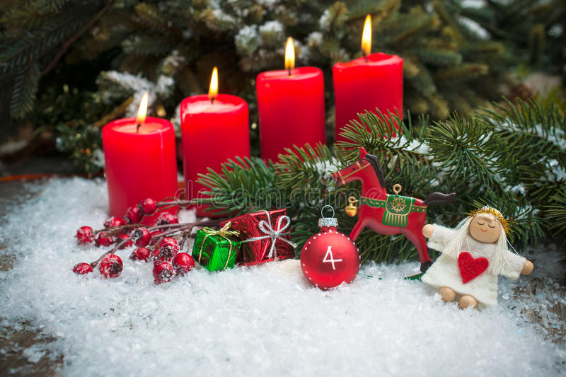 Red candles burning in snow for fourth advent. Christmas tree branches and candle for advent season four candles burning stock images