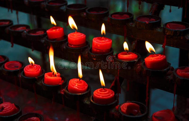 Red candles with yellow flame on catholic church altar. Burning candle closeup photo. In memoriam banner template. Christian church altar closeup. Religious stock images