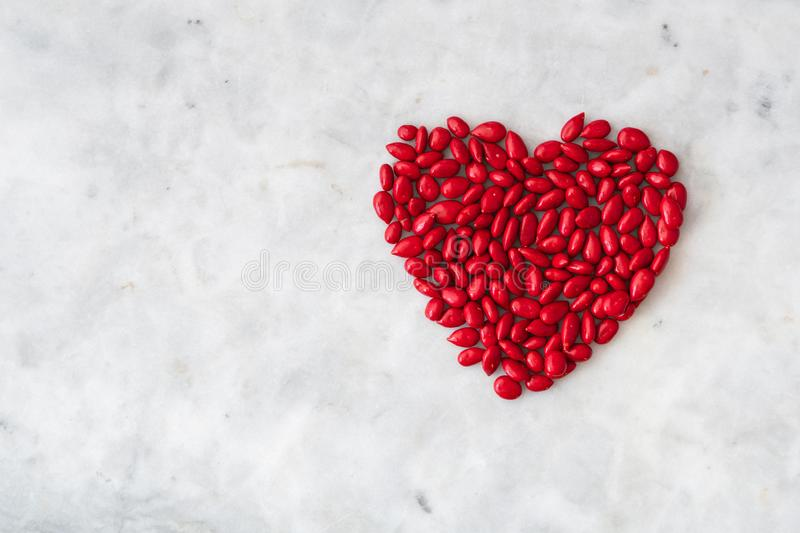 Red candy coated sunflower seeds in a heart shape on a white granite background royalty free stock images