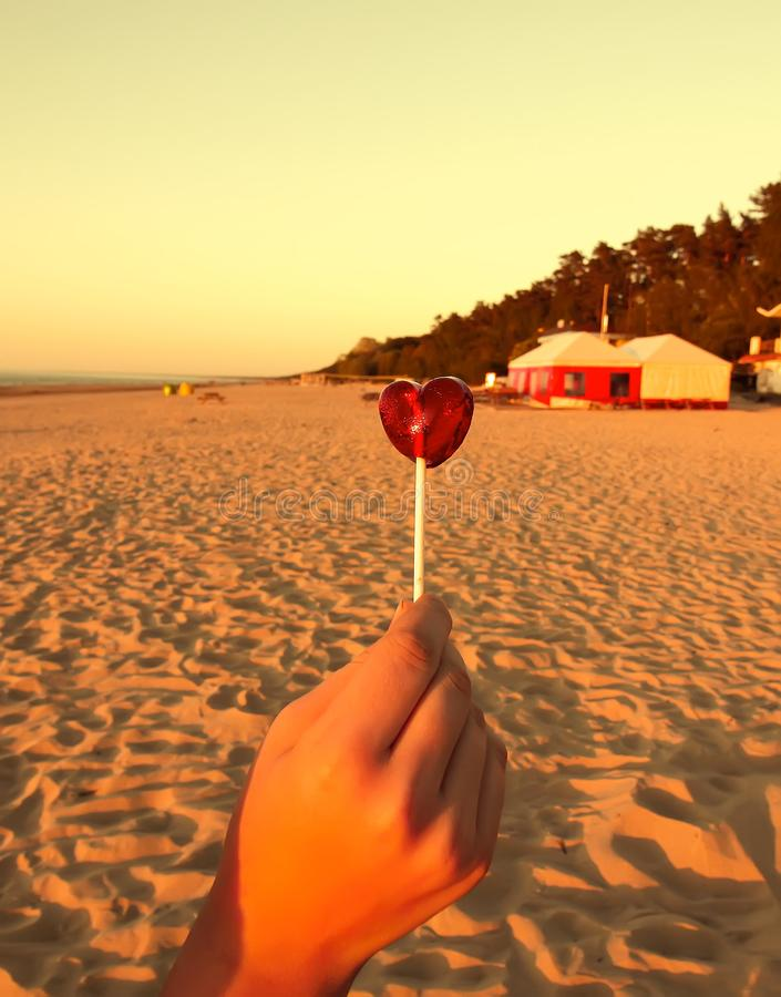 Red candy in shape of a heart in a hand on sandy beach background. Sunset warm light. Vertical shot. Red candy in the shape of a heart in a hand on sandy beach royalty free stock image
