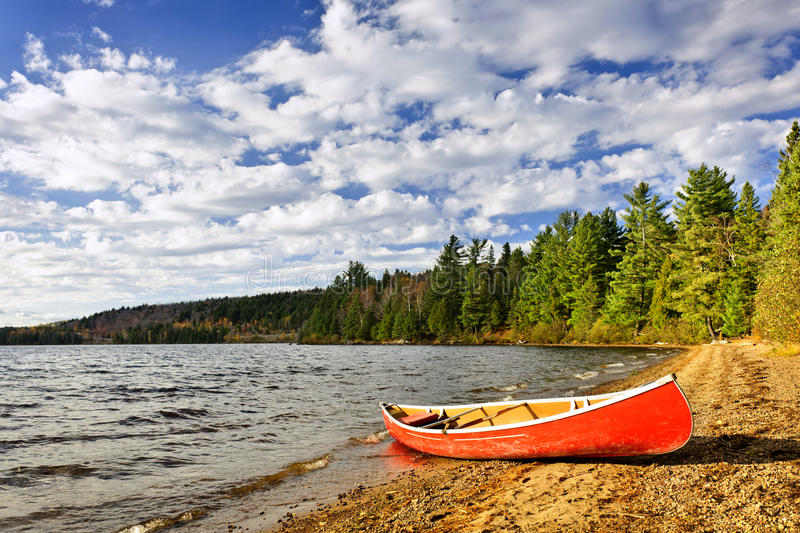 Red canoe on lake shore royalty free stock images