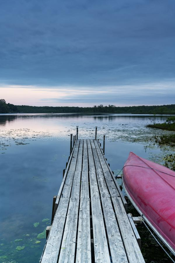 Red canoe tied to rustic wooden dock leading out to calm lake un. Der overcast sunset sky. Nature, simplicity and camp scene royalty free stock photo