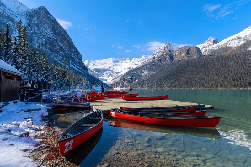Red canoes at Lake Louise with rocky mountain in Banff national park. Alberta, Canada - October 7, 2018 : Red canoes at Lake Louise with rocky mountain in Banff royalty free stock photo