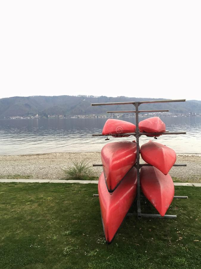 Red canoes on a shelf. In front of Lake Constance - ready for water sport activities on the lake royalty free stock images