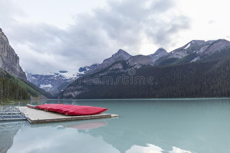 Canoes in the lake. Red canoes on a wooden jetty next to a turquoise water lake with high mountains next to it on a cloudy day stock images