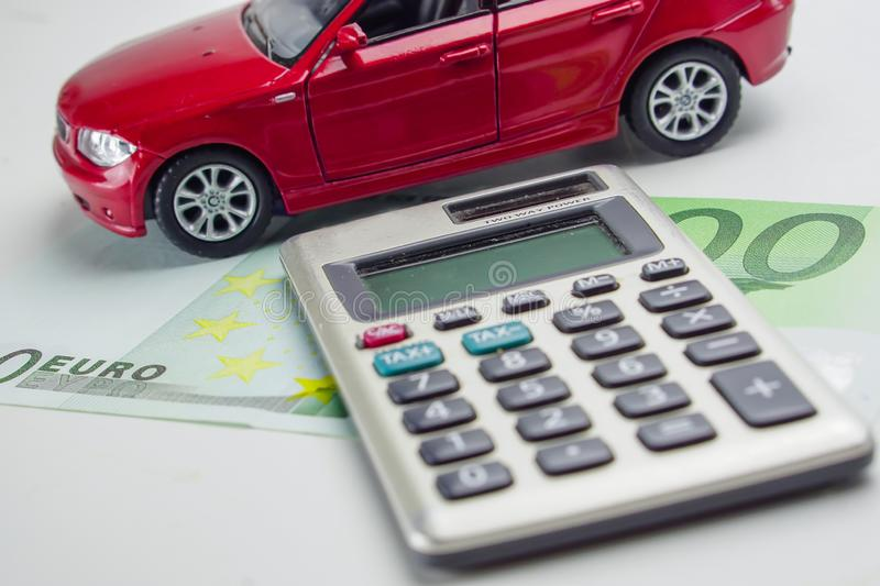 Red car and calculator on Euro Banknote. Car loan, Finance, saving money, insurance and leasing time concepts royalty free stock image