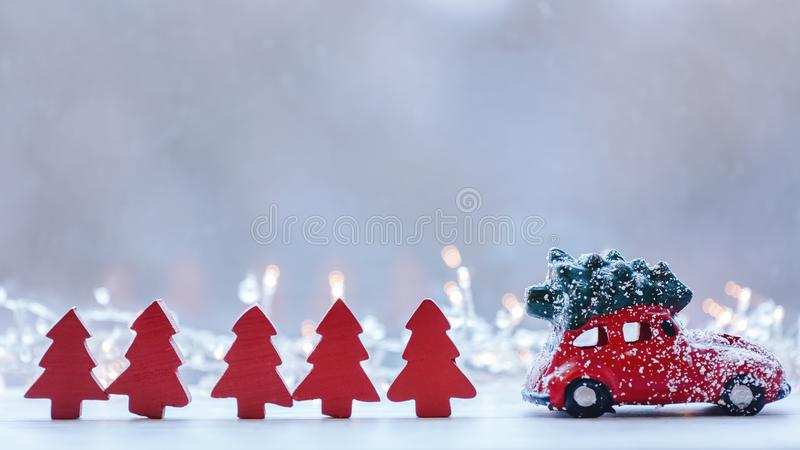 Red car with Christmas tree on roof on bright lights background.  Christmas motif.  Wooden figures of red Christmas trees. stock photography